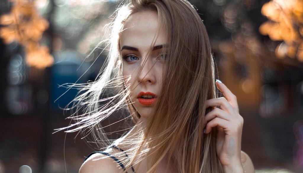 Imagem de uma jovem segurando o cabelo.