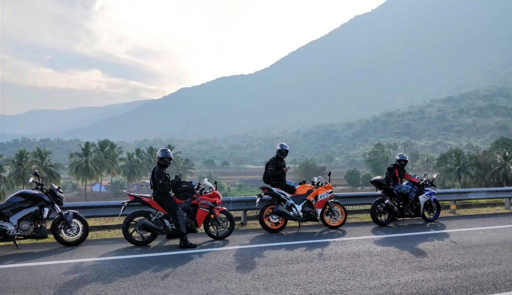 Quatro motos paradas no acostamento de uma rodovia com três motociclistas.