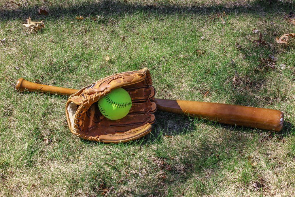 taco de beisebol de madeira no gramado ao lado de luva e bola