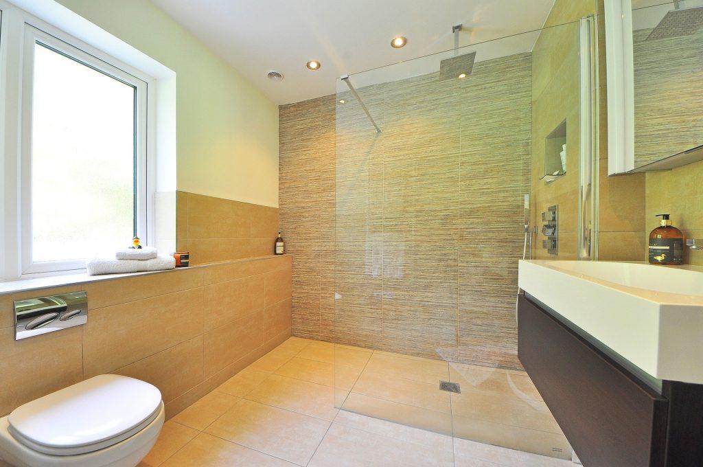 Um vaso sanitário em um banheiro de luxo com janela, área de chuveiro e pia