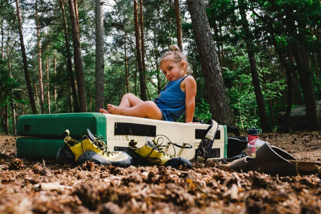 Imagem mostra uma meninnha posando para a foto enquanto está sentada sobre uma maleta grande, que por sua vez está sobre o chão repleto de folhas secas de uma floresta.
