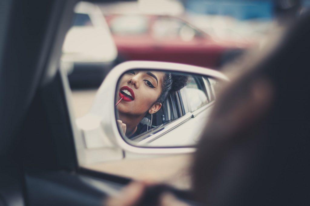 Na foto uma mulher aplicando batom em frente a um retrovisor de carro.
