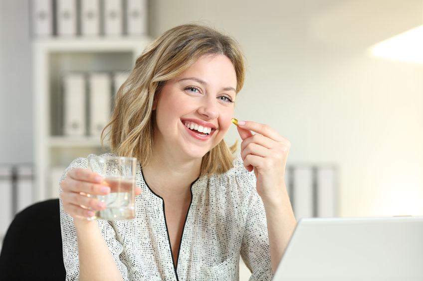 Imagem de uma mulher tomando uma cápsula.