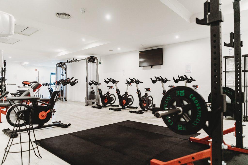 Imagem mostra uma sala de academia desocupada, com uma série de bicicletas ergométricas montadas, entre outros equipamentos.