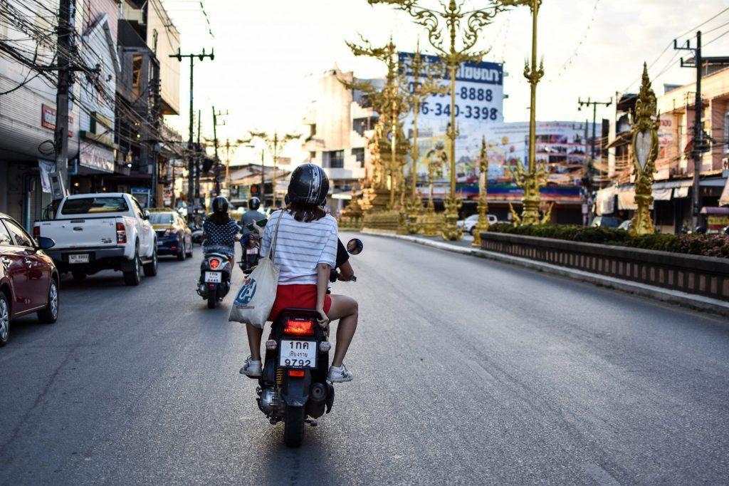 Imagem mostra duas pessoas em uma motocicleta em movimento.