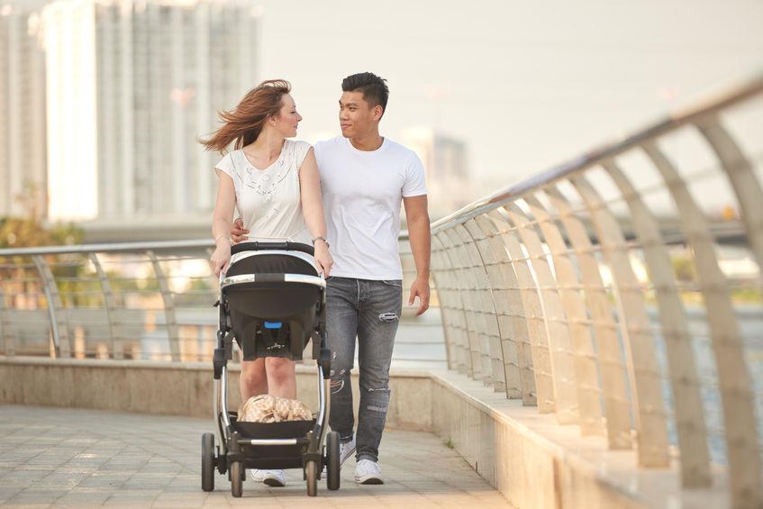 Pai e mãe passeando com carrinho de bebê em ponte.