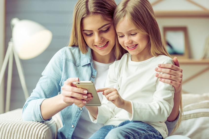 Imagem de uma mulher com sua filha mexendo em um celular.