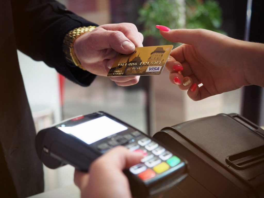 Pessoa entregando cartão para um vendedor utilizar na maquinha de pagamento.