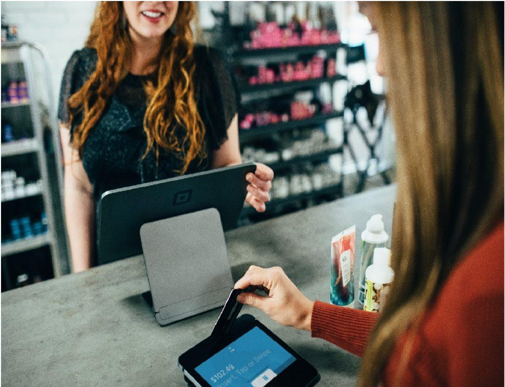 Mulher pagando com cartão e funcionária passando na maquinha.