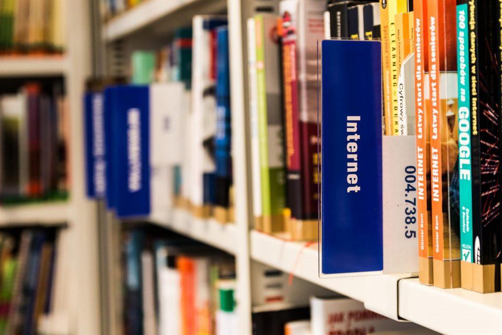 Na foto livros dentro de uma biblioteca em uma estante.