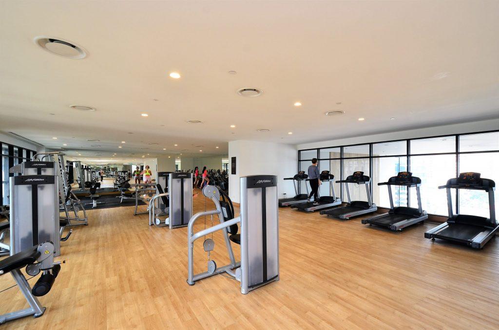 Imagem mostra uma sala de uma academia, com piso de taco de madeira, e uma fileira de esteiras profissionais de frente para janelas altas.