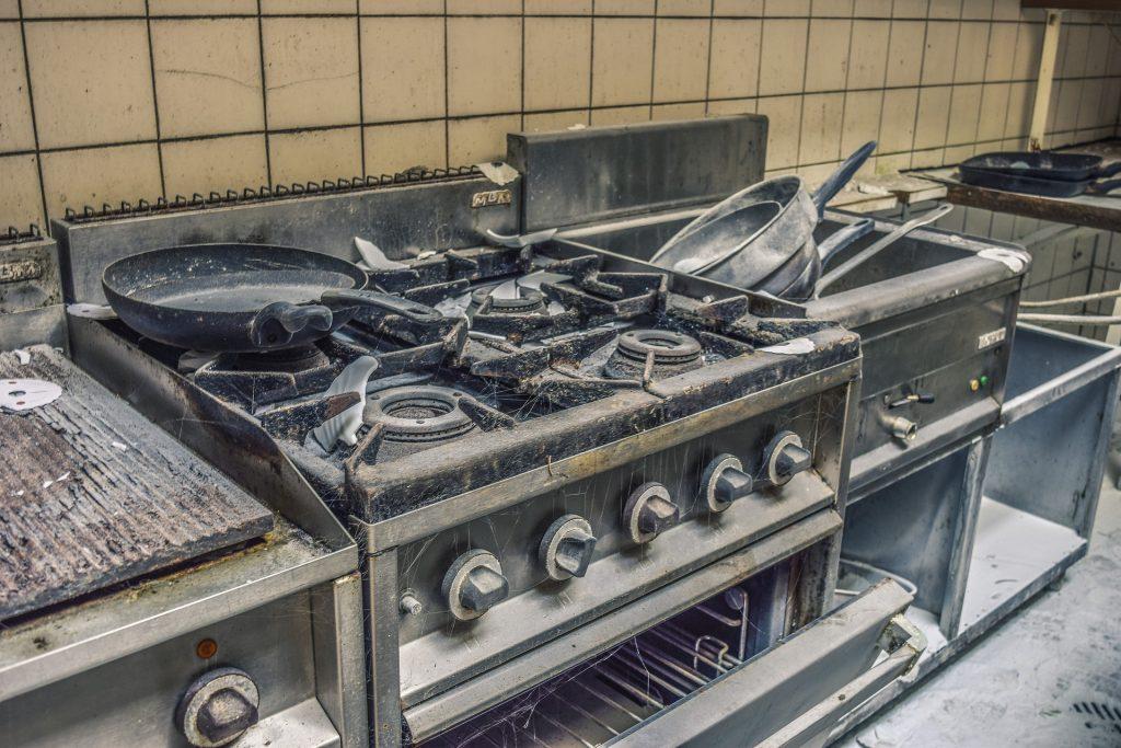 Imagem mostra um fogão industrial extremamente sujo.