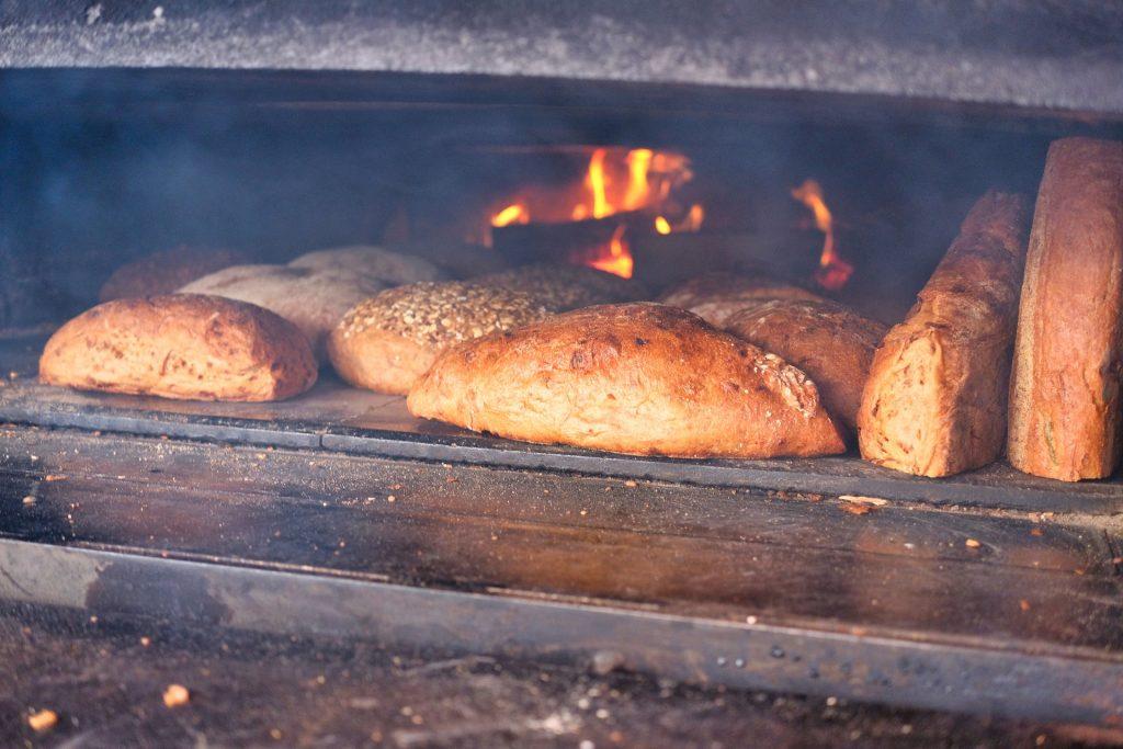 Imagem mostra um forno a lenha assando pães
