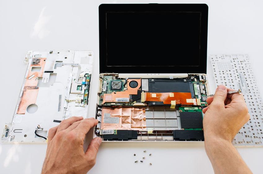 Mãos com chave de fenda trabalham em ajuste de componentes internos de notebook