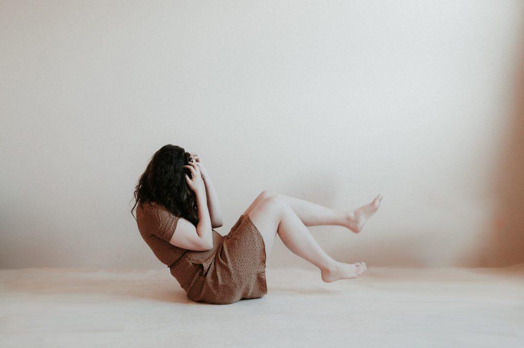 Mulher sentada no chão com as mãos no rosto.
