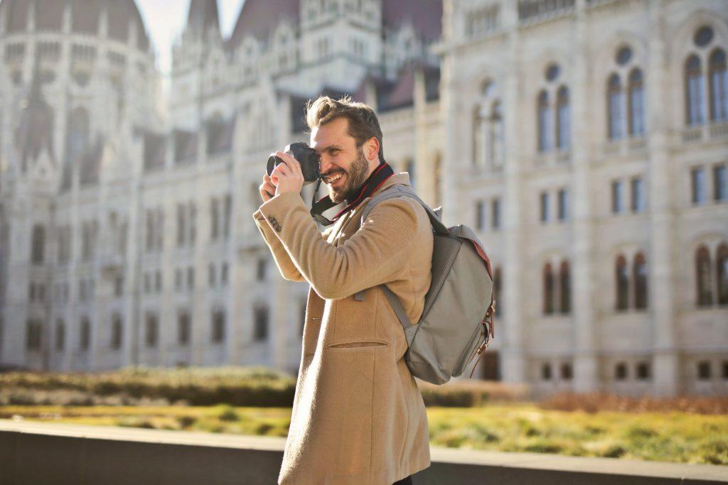 Imagem de um homem fotografando com uma mochila nas costas.