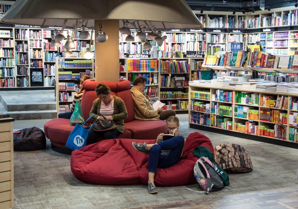 Imagem mostra três pessoas sentadas em um espaço de descanso de uma livraria. Duas lêem livros, enquanto outra mexe em sua bolsa.