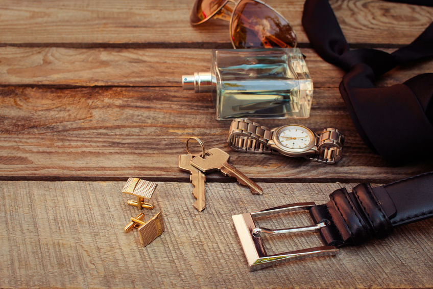 Itens masculinos como perfume, cinto, chave, gravata, relógio e óculos sobre superfície de madeira.