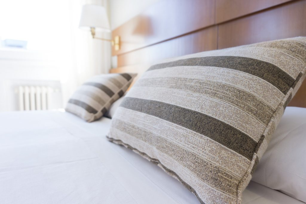 Na foto uma cama com lençol branco, almofadas listradas e cabeceira em madeira.