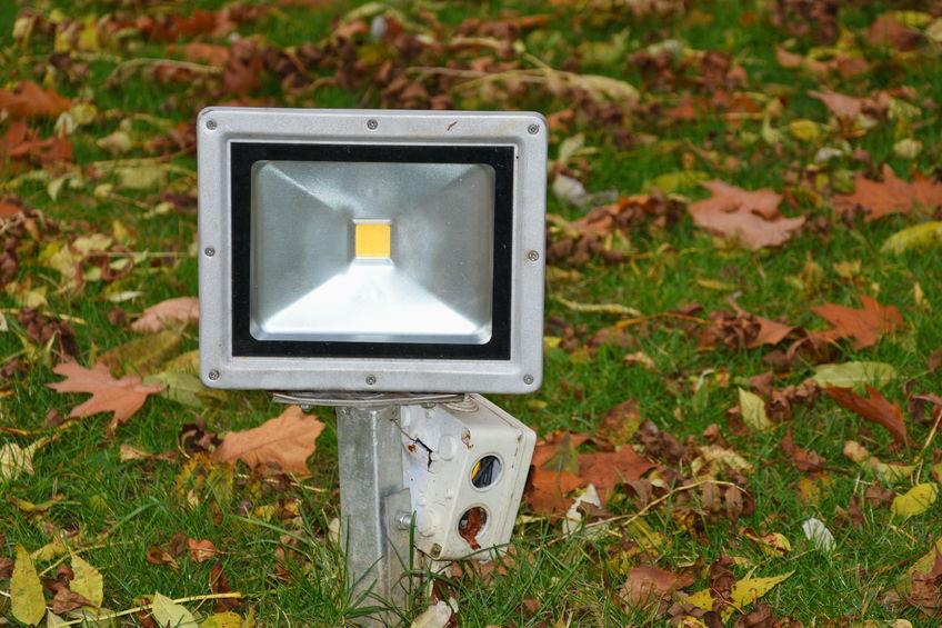 Imagem mostra um refletor LED no chão de uma área com grama.