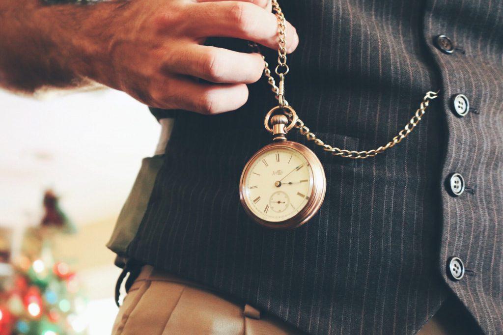 Na foto um homem tirando um relógio de bolso de um colete.