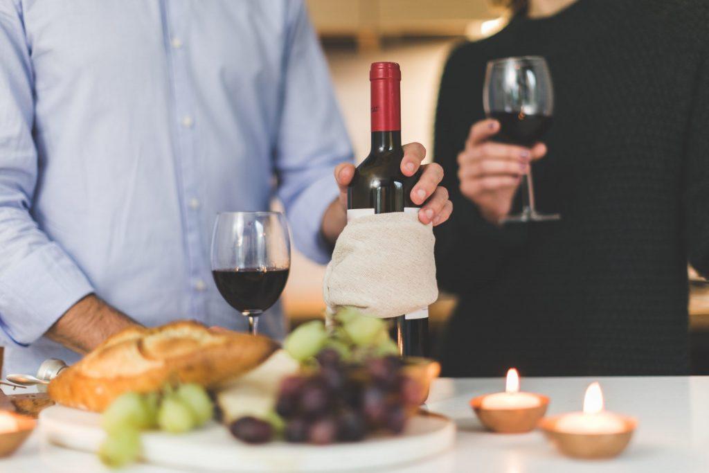Casal com garrafa de vinho, taças , uvas e pães.