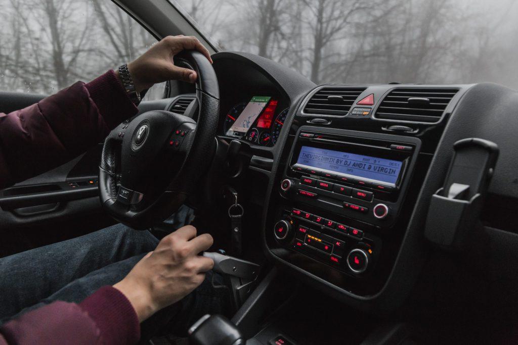 Imagem mostra um carro sendo pilotado na estrada, com foco no sistema de som ligado, com a tela informando o nome da música sendo executada.