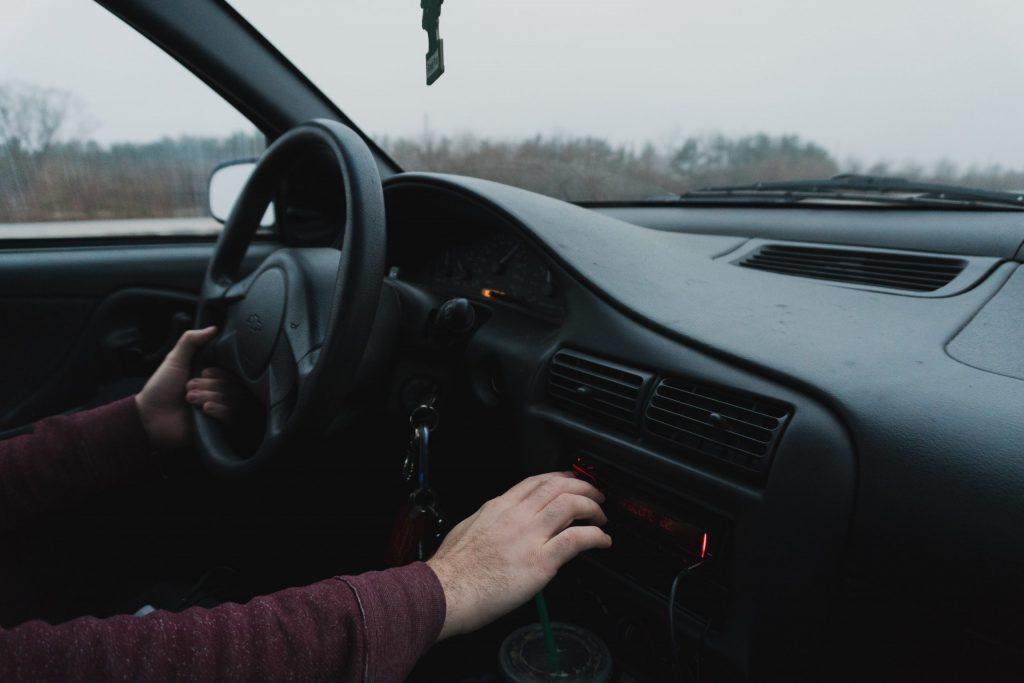 Imagem mostra a mão do piloto de um carro manuseando os controles do seu sistema de som.