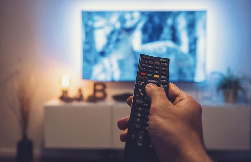 Pessoa segurando controle remoto e TV está em segundo plano desfocada.