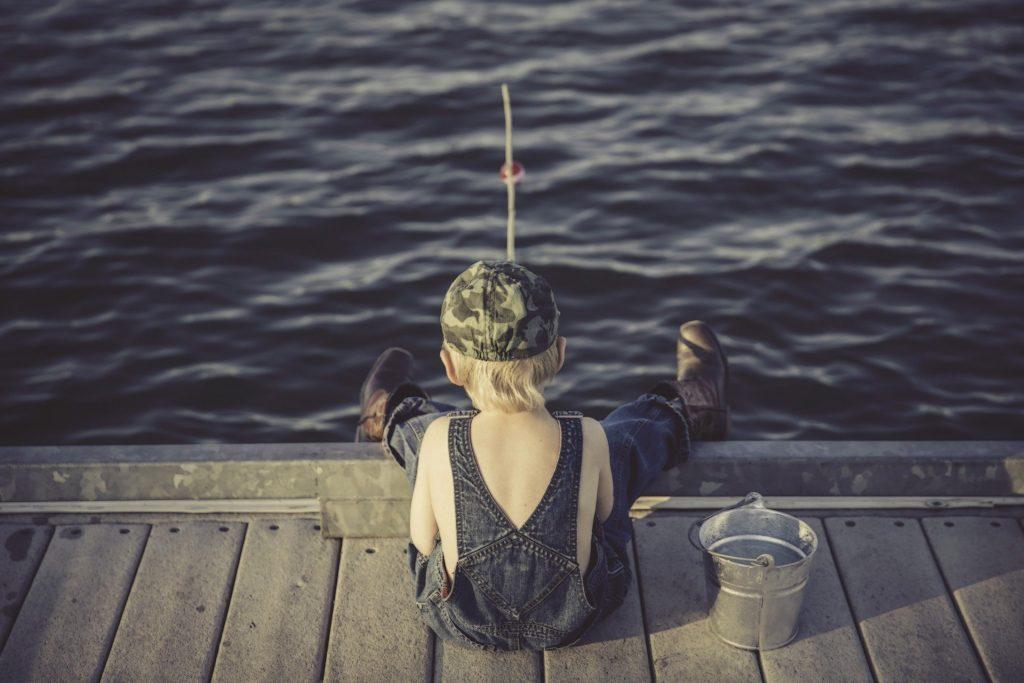 Imagem mostra um menino pescando em uma plataforma.