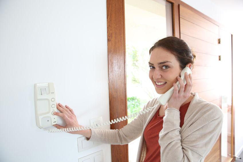 Imagem mostra uma mulher usando um interfone comum.