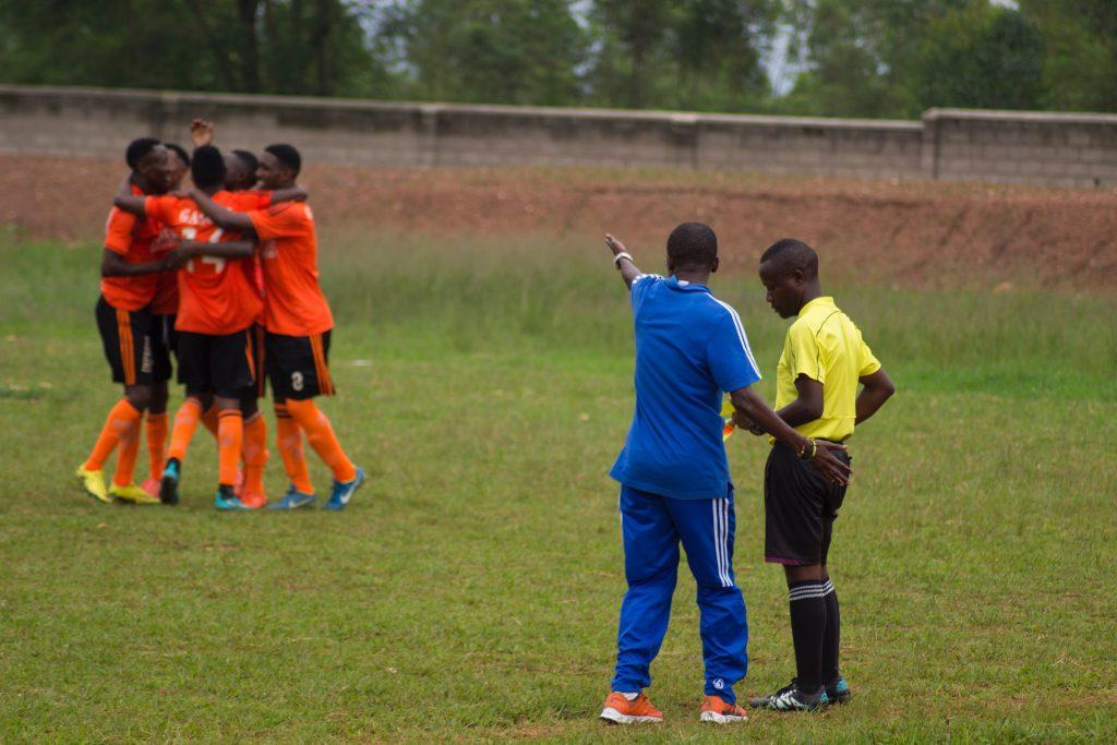 Imagem mostra um momento de uma partida de futebol. No primeiro plano, um treinador conversa com um árbitro; no segundo, um grupo de jogadores se abraça, comemorando um gol.