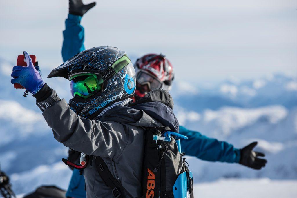Imagem mostra duas pessoas, com equipamentos para esportes radicais de neve, tirando uma selfie.