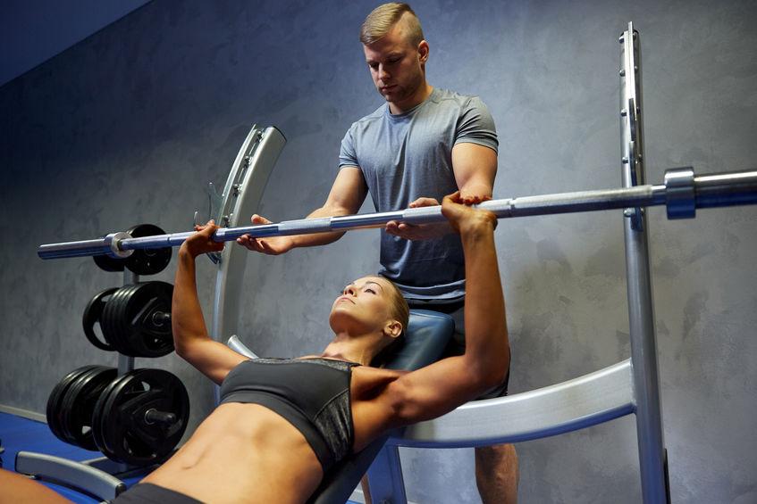 Imagem mostra uma mulher, deitada num banco supino reclinável, fazendo levantamento de barra, com o auxílio de um personal trainer.