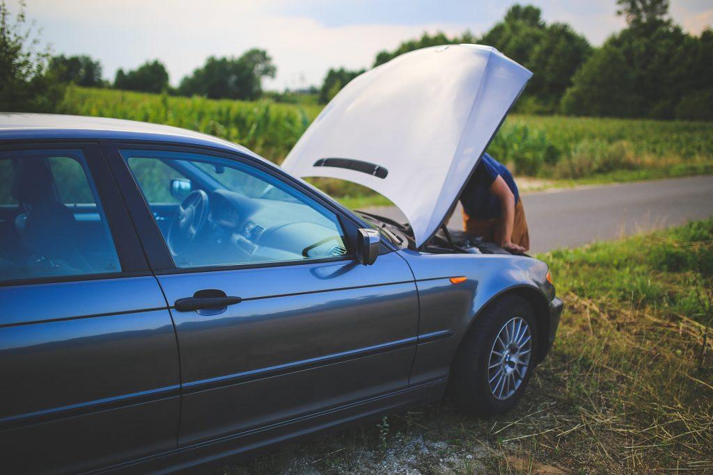 Um carro parado nas margens de uma estrada com o capô aberto para inspeção do compartimento do motor.