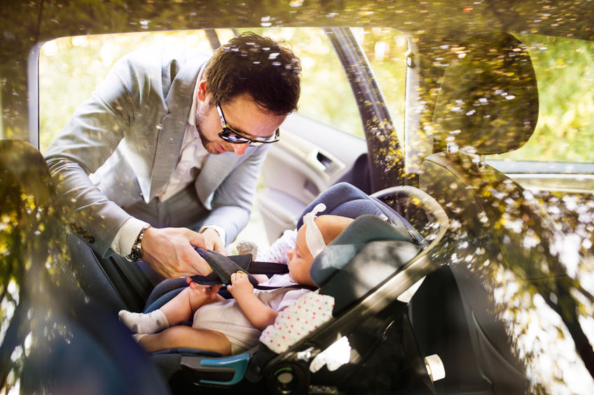 Pai ajustando bebê dentro do carro.