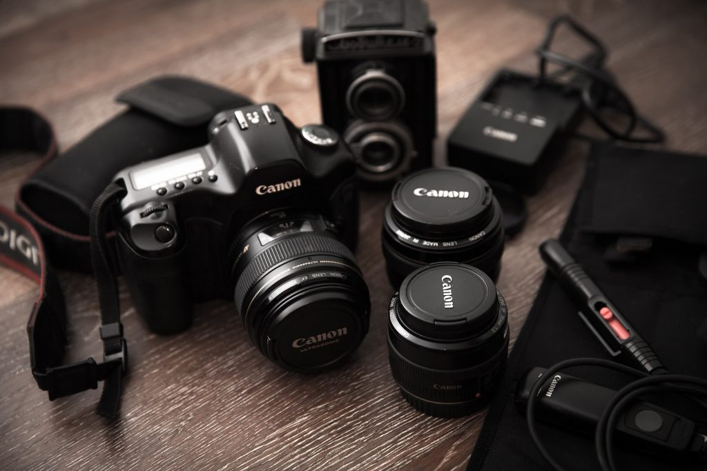 Câmera, lente e outros acessórios da Canon sobre uma superfície de madeira.