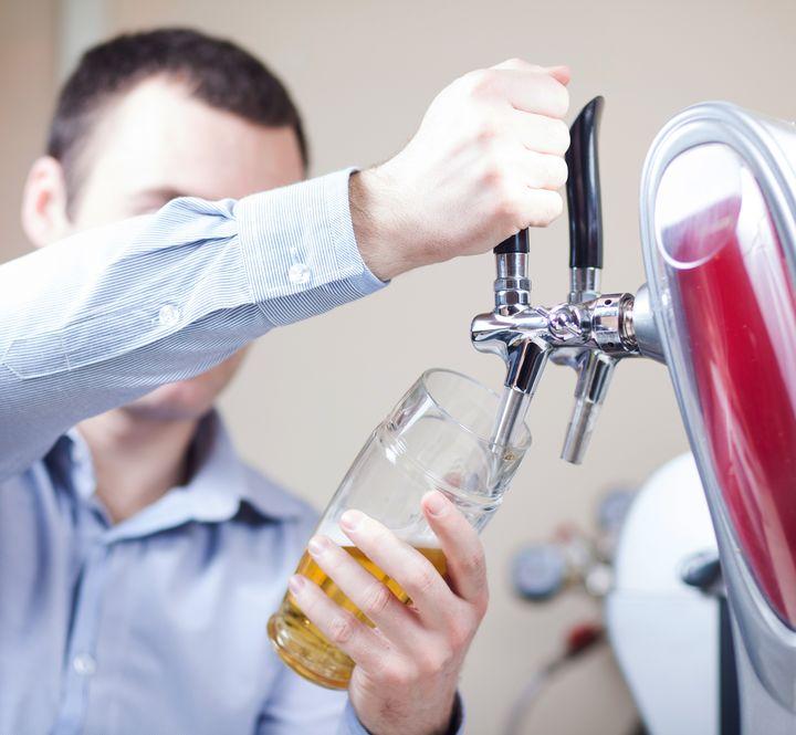Imagem mostra homem enchendo um copo de vidro numa chopeira de duas torneiras.