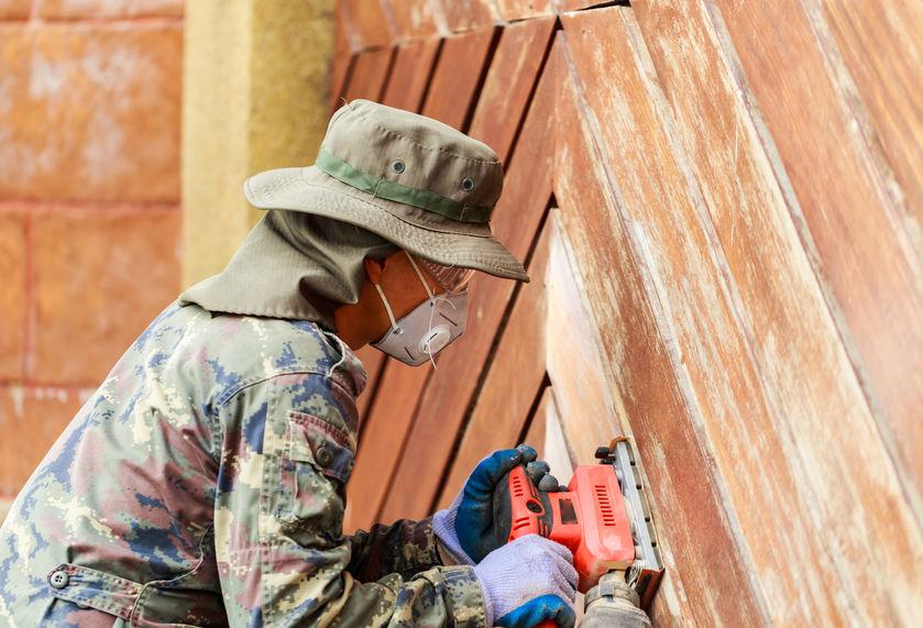 Homem equipado com óculos e máscara de proteção usando uma lixadeira orbital em madeira