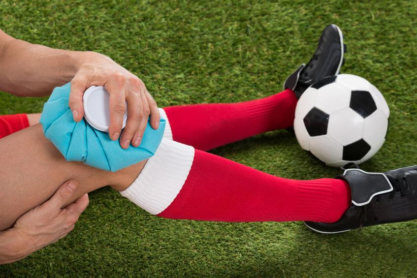 Imagem mostra o corte do tronco e pernas de uma mulher que ajusta o meião da perna direita, com as mãos logo abaixo do joelho. A mão de uma outra pessoa mira um spray na região.