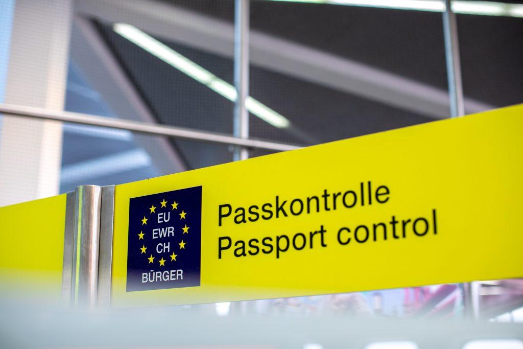 Placa de imigração em aeroporto com bandeira da União Europeia.