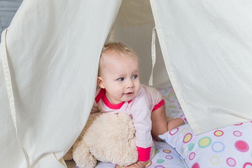 Imagem mostra um bebê olhando surpreso para fora do quadro. Ele está engatinhando sobre camadas de cobertores e travesseiros de uma barraca caseira.