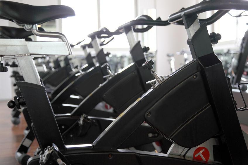 Imagem mostra o close de uma bicicleta ergométrica, que forma uma fileira com outras bicicletas ao fundo, desfocadas e em segundo plano.