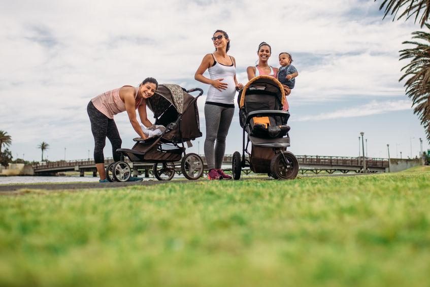Mamães passeando com seus bebês em carrinho em um parque.