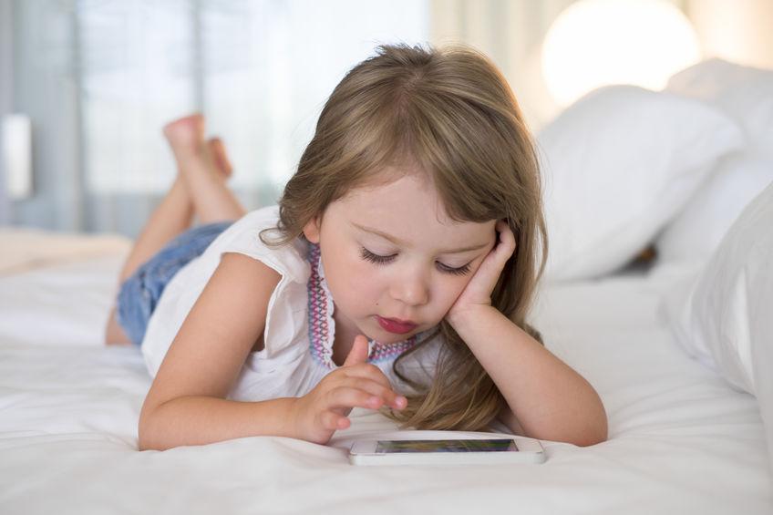 Imagem de uma criança usando celular.