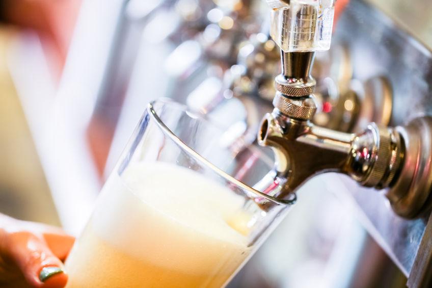 Imagem mostra, em foco seletivo, um copo de vidro de boca larga sendo enchido por uma torneira de uma chopeira, com outras torneiras enfileiradas e desfocadas ao fundo.