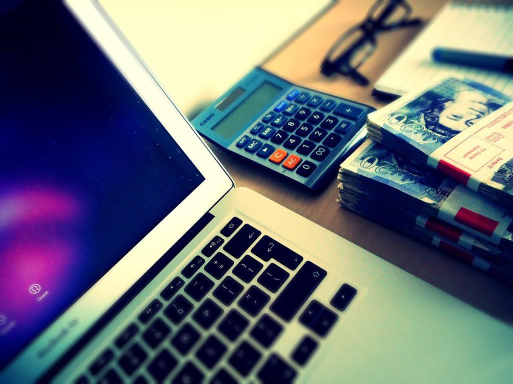 Notebook, várias notas de dinheiro e calculadora.