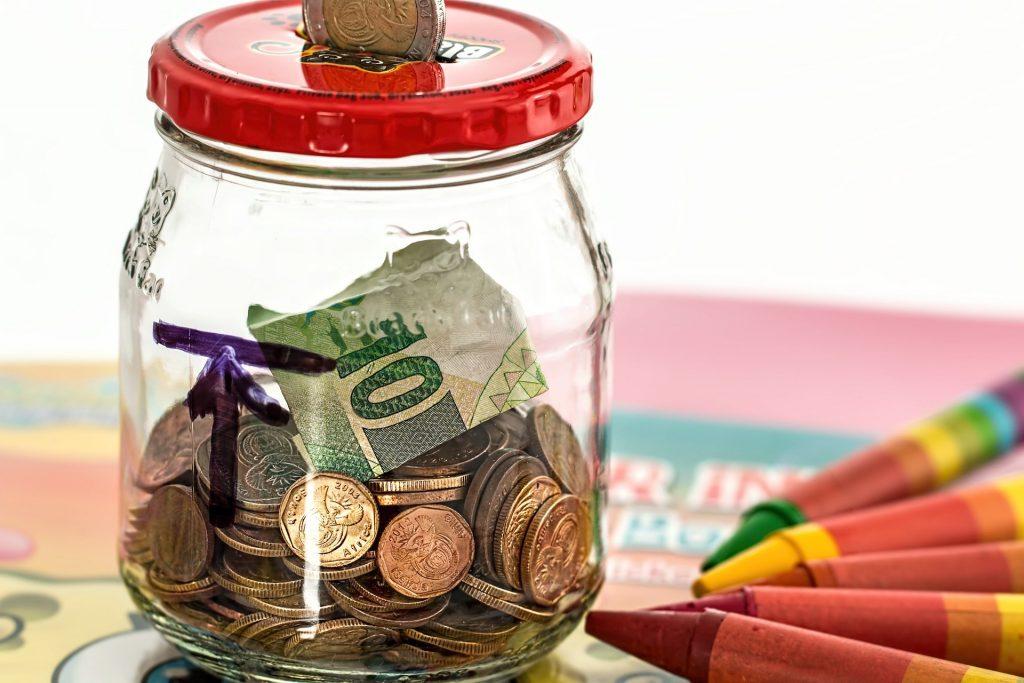 Cofrinho de vidro com moedas.