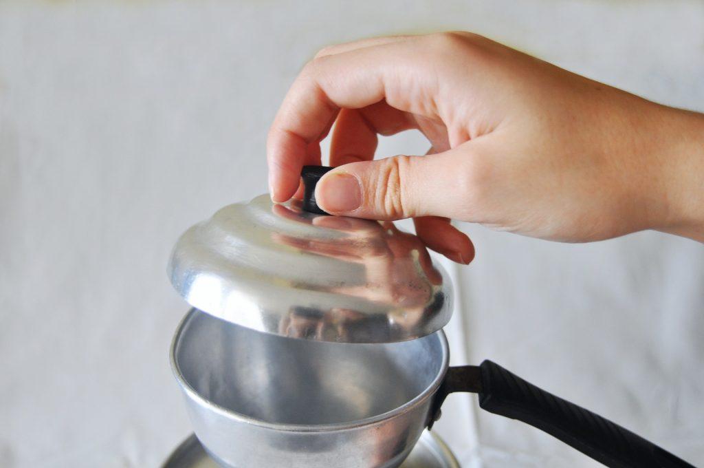 Imagem de mão abrindo tampa de cuscuzeira individual