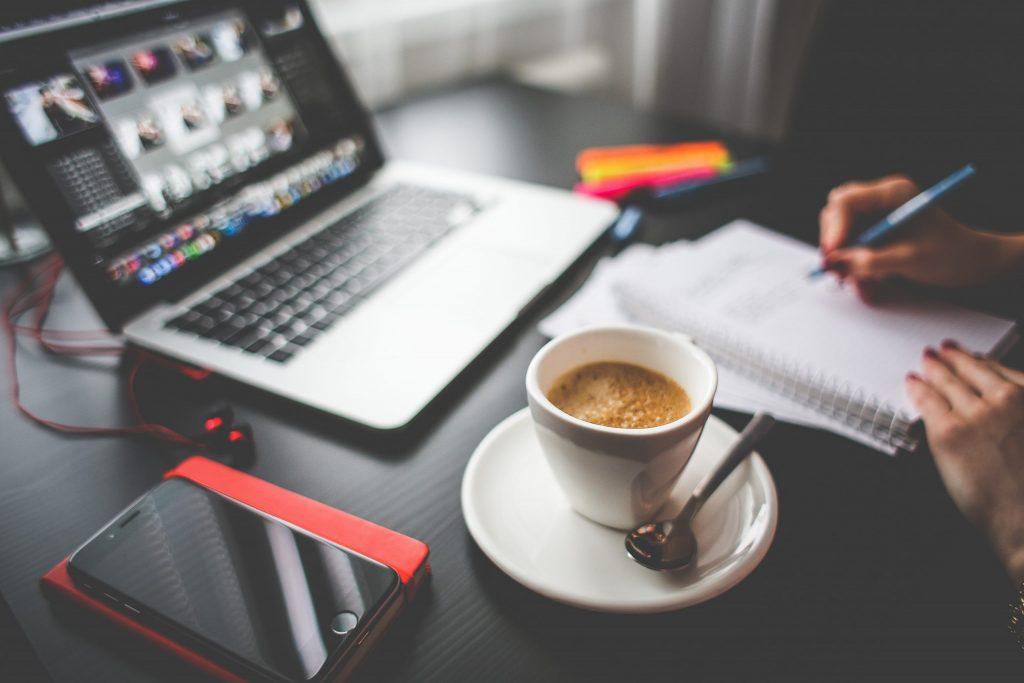 Pessoa escrevendo no caderno sobre mesa com notebook, celular e xícara de café.